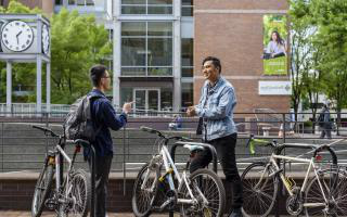 Two students talking at a bike rack
