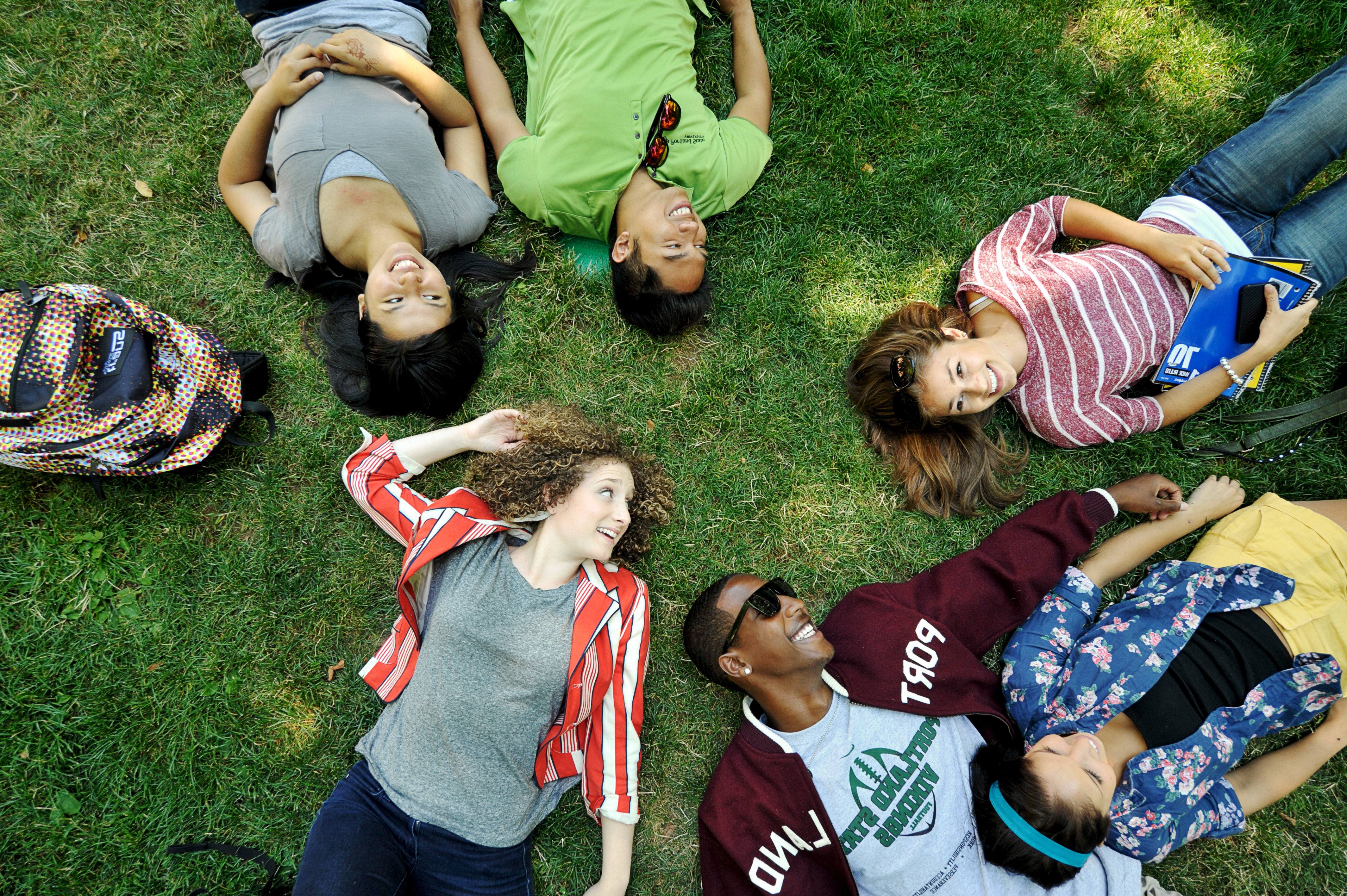 Diverse group of PSU students laying on the grass in the PSU Park Blocks.