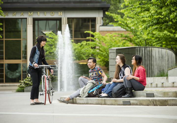 PSU Students sitting outside on campus; one student is holding a bike.